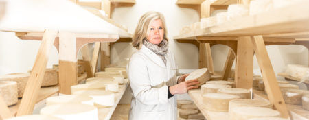 woman in a cheese factory holding cheese
