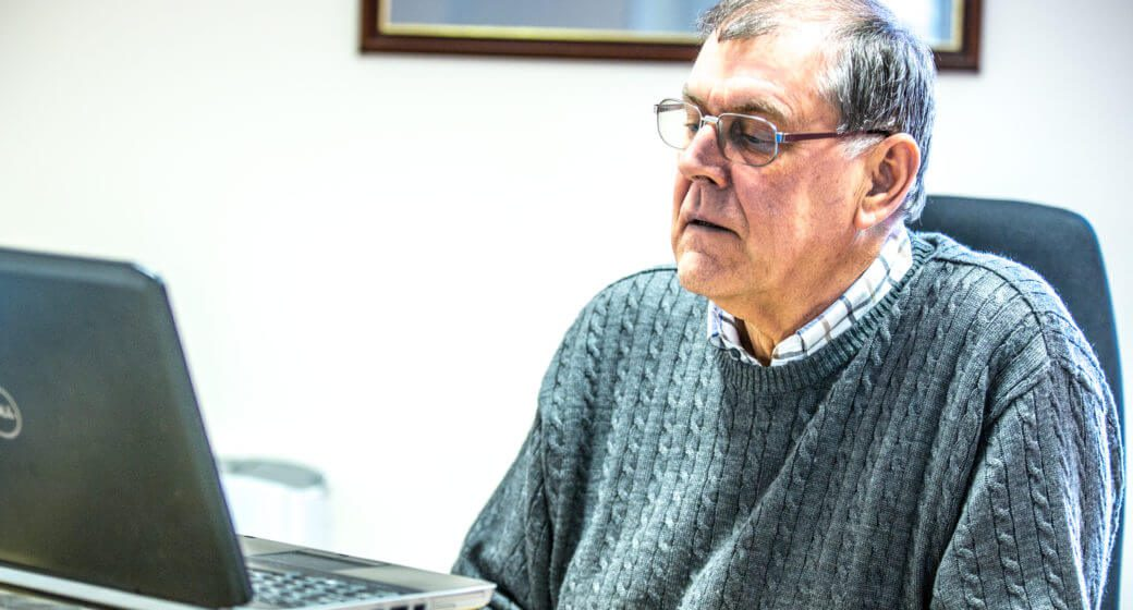 man sat at desk looking at laptop swindells east sussex accounting and tax