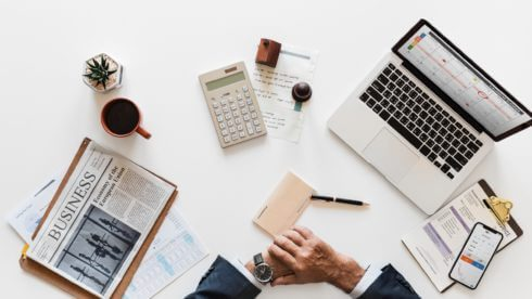 Man sat at desk surrounded by laptop and paper swindells east sussex accounting