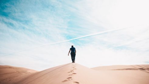Man walking up sand dune in the desert